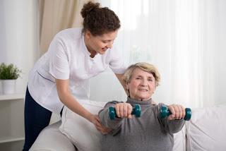 Caregiver providing assistance with senior exercises