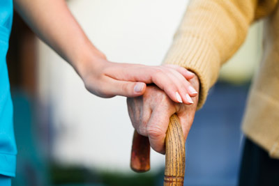Compassionate caregiver holding hands with senior